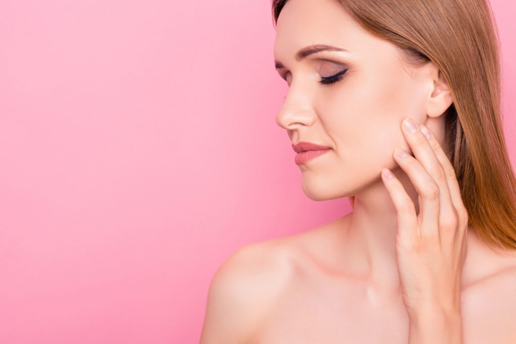 Getönte Tagescreme von Utsukusy Cosmetics / Junge Frau vor rosa Hintergrund